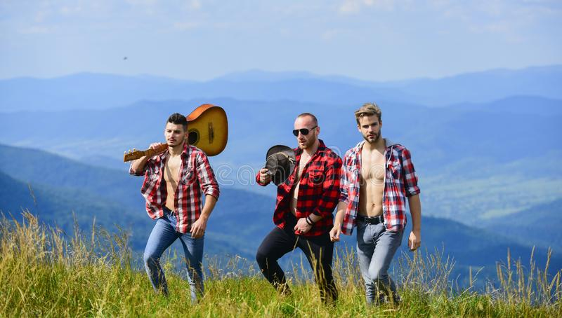 Group of young people in checkered shirts walking together on top of mountain. Tourists hiking concept. Hiking with. Friends. Friendly guys with guitar hiking stock photo