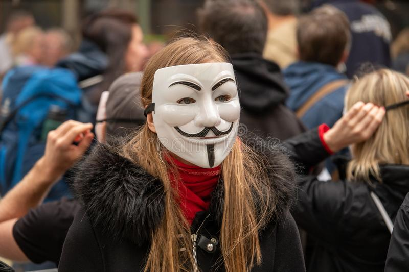 Group of young people dressed all in black goes out on the street to demonstrate with anonymous masks royalty free stock photo