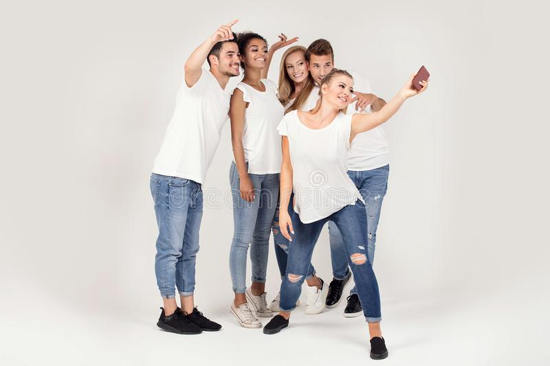 Group of young smiling people taking selfie. Group of young people enjoy their company, smiling, having fun together, taking selfie by mobile phone royalty free stock images