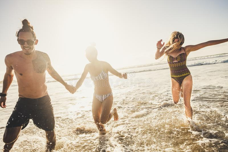 Group of young people friends enjoying with fun the summer holiday vacation running at the beach to the water in playful outdoor. Leisure activity together stock photography