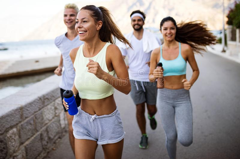 Group of young people friends running outdoors at seaside royalty free stock images