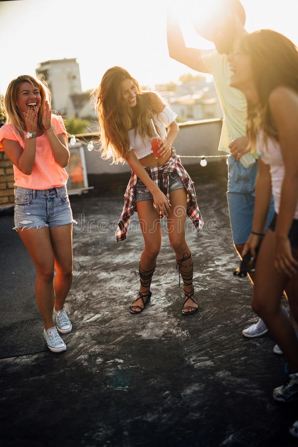 Group of young people having fun at a summertime party, at sunset stock photography