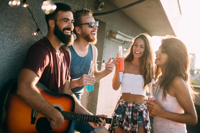 Group of young people having fun at a summertime party, at sunset stock photo