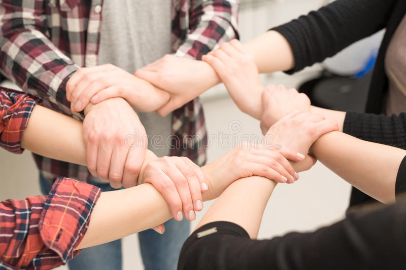 A group of young people hold strong hands. stock photography
