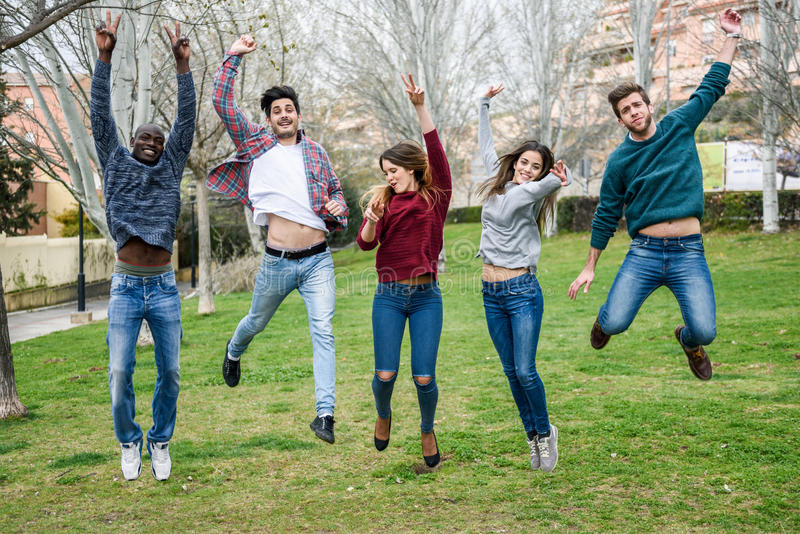 Group of young people jumping together outdoors royalty free stock photos