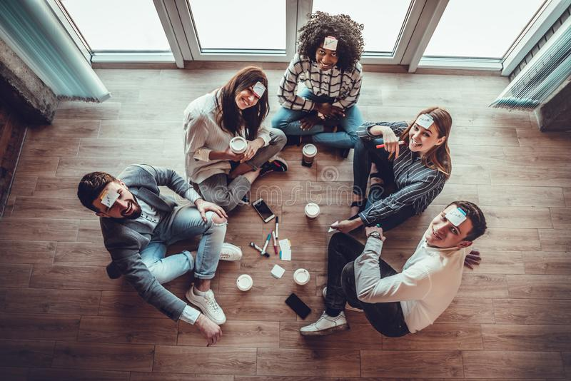Group of young people in office floor having fun playing name game with sticky notes to their forehead. Top view, female, team, casual, sitting, smiling royalty free stock image