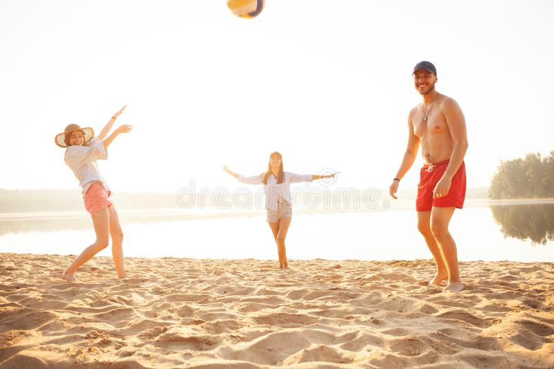 Group of young people playing with ball at the beach. Young friends enjoying summer holidays on a sandy beach royalty free stock photo