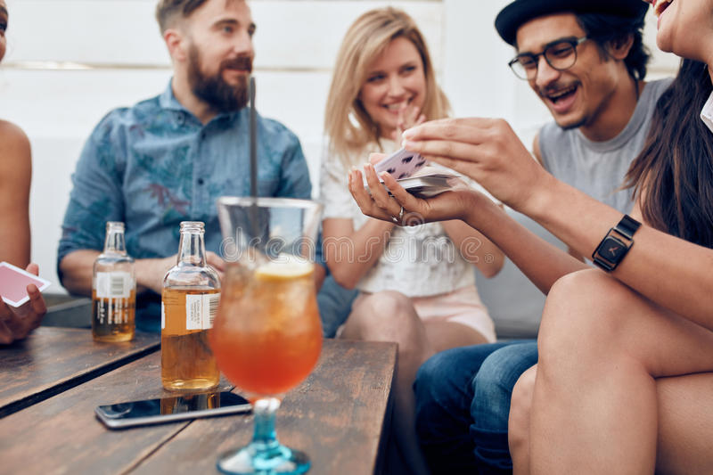 Group of young people playing cards royalty free stock images