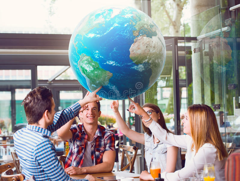 Group of young people pointing at planet Earth. Sitting at the table stock photo