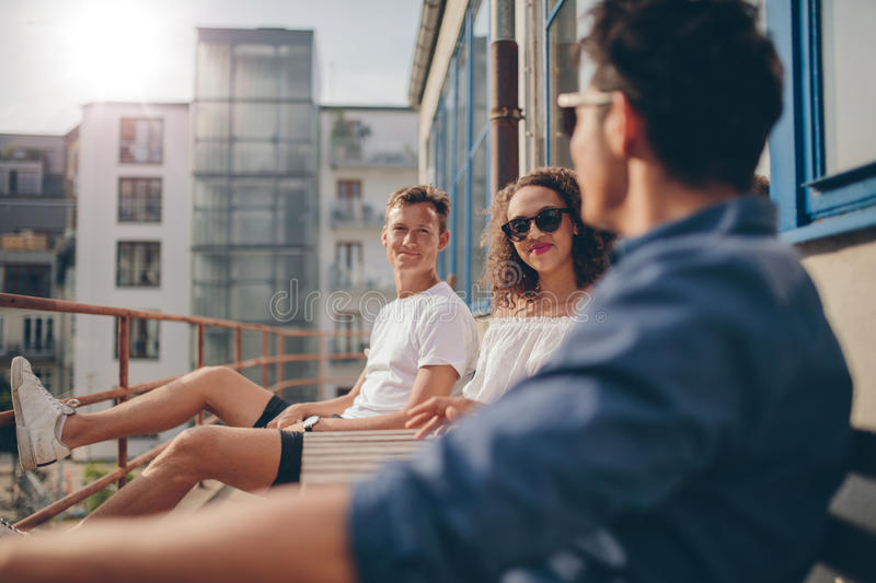 Group of young people relaxing in a balcony. Shot of young women sitting with her friends at outdoor cafe. Group of young people relaxing in a balcony stock photos