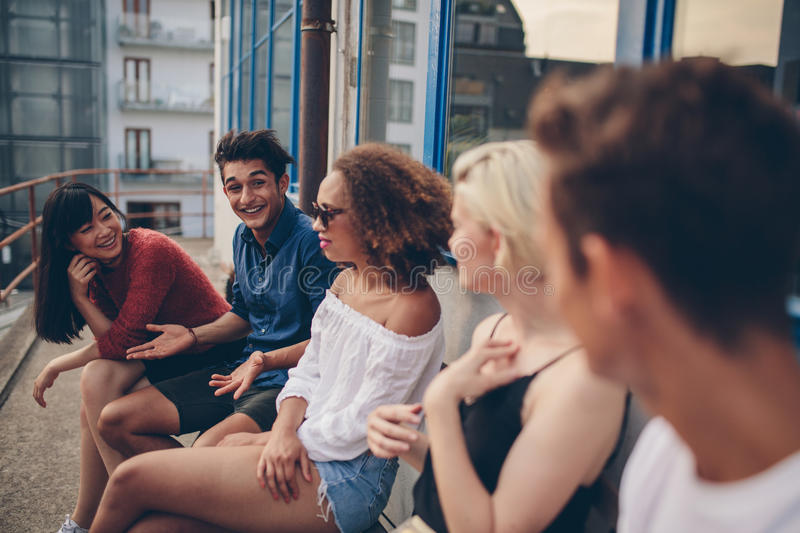 Group of young people relaxing in terrace. Multiracial group of friends sitting in balcony. Young people relaxing outdoors in terrace royalty free stock images