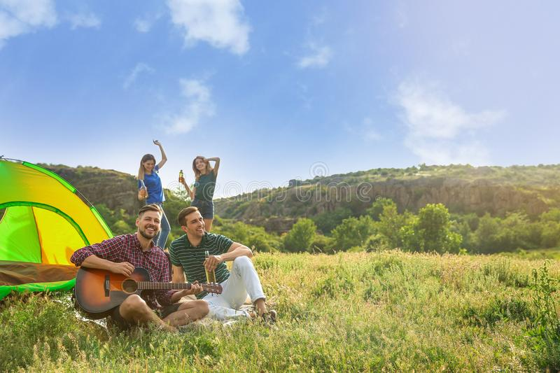Group of people resting with beer and guitar near camping tent in wilderness. Group of young people resting with beer and guitar near camping tent in wilderness stock photo