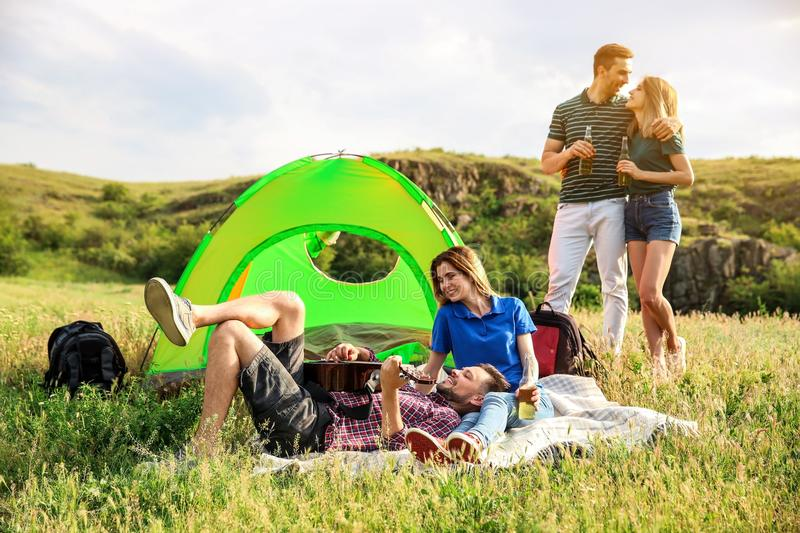 Group of young people resting with beer and guitar. Near camping tent in wilderness royalty free stock photos