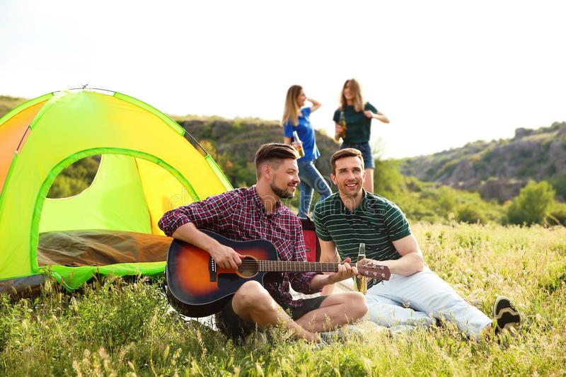 Group of young people resting with beer and guitar. Near camping tent in wilderness royalty free stock photography