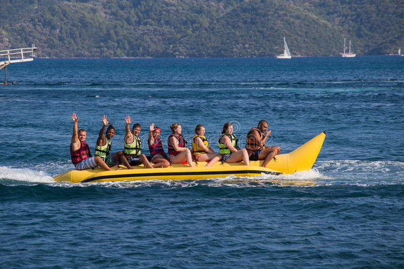 Group of young people riding banana boat stock photo