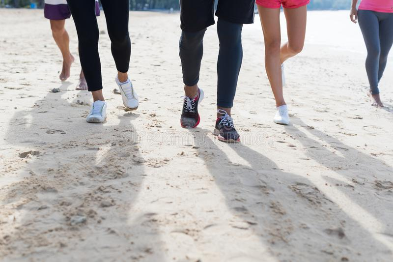 Group Of Young People Running On Beach Feet Closeup Sport Runners Jogging Working Out Team Training Together. On Seaside stock images