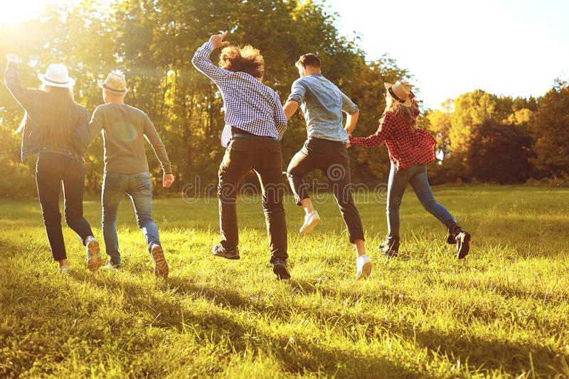 A group of young people running through the park. royalty free stock images