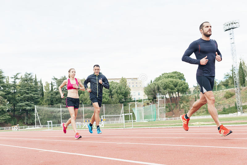 Group of young people running on the track field royalty free stock photo
