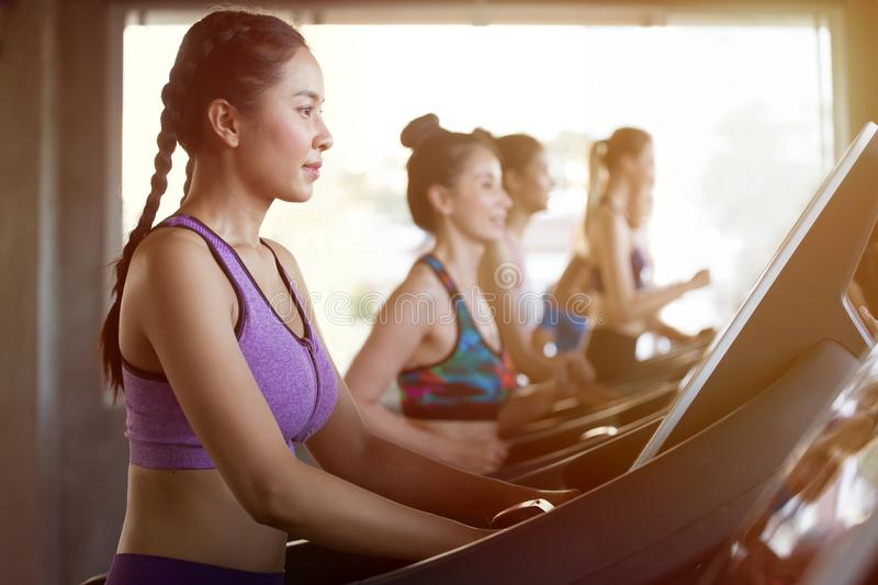group of young people running on treadmills in sport gym .fitness woman runner on running machine in morning time royalty free stock photography