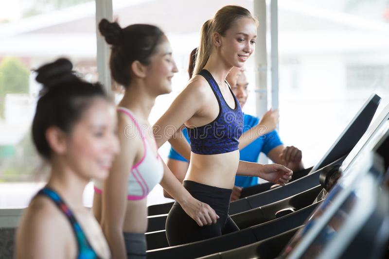 group of young people running on treadmills in sport gym .fitness woman runner on running machine with trainer man in morning time stock image