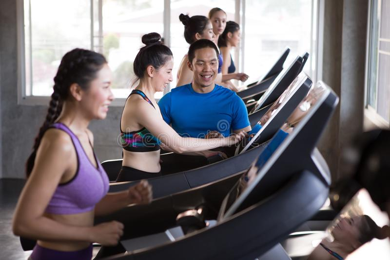 group of young people running on treadmills in sport gym .fitness woman runner on running machine with trainer man in morning time royalty free stock image