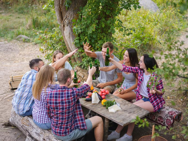 Group of young people sitting around a table outside. They enjoy to chat and drink beers. royalty free stock photography