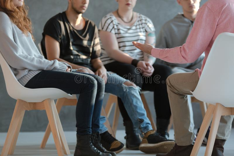 Group of young people sitting in a circle and talking to a psych royalty free stock images