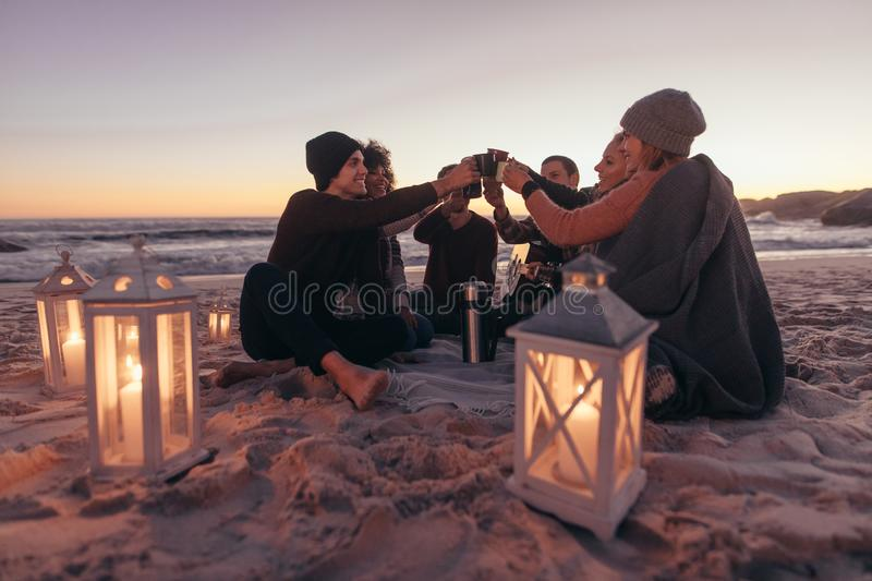 Friends partying at the beach with coffee stock images