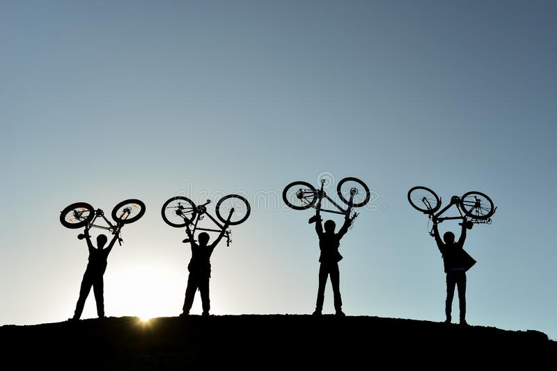 Four men each holding a bicycle aloft royalty free stock images