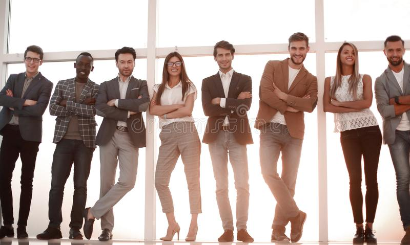Group of young people standing in an office with a large window. The concept of employment stock image