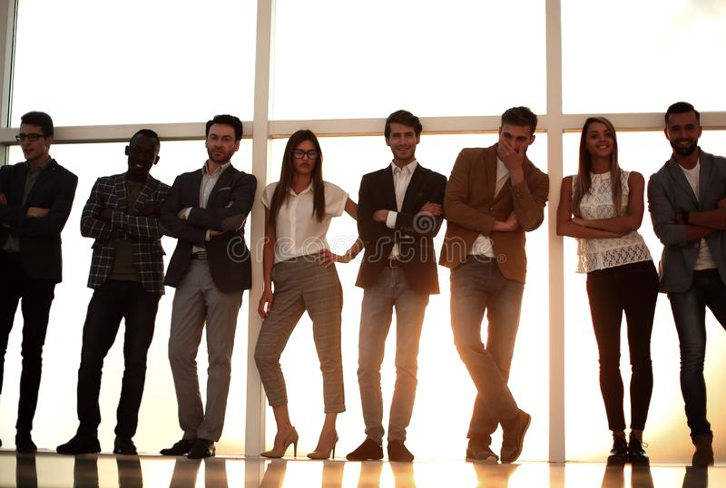 Group of young people standing in an office with a large window stock images