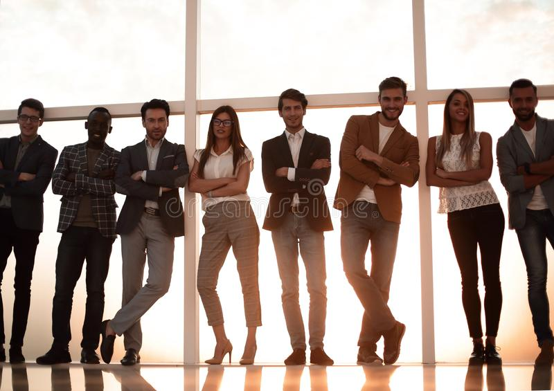 Group of young people standing in an office with a large window stock image