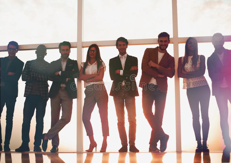 Group of young people standing in an office with a large window royalty free stock photography