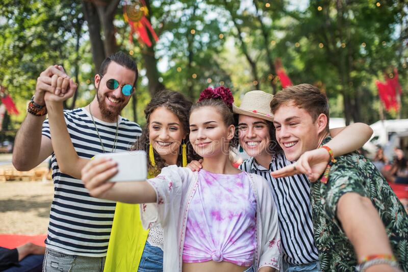 Group of young people at summer festival, taking selfie with smartphone. royalty free stock images