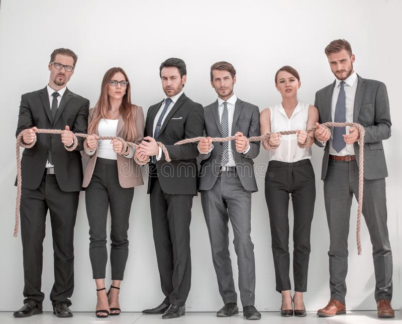 Group of young people tied with a strong rope. Photo with copy space royalty free stock images