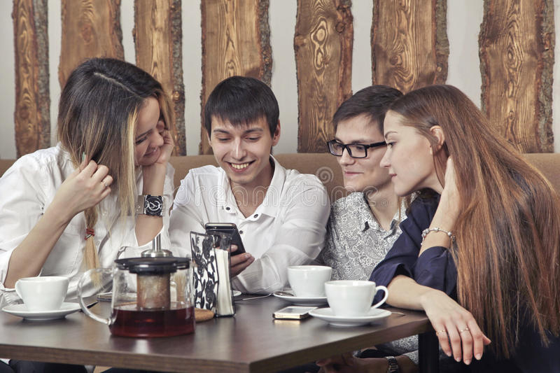 Group of young people from two couples of guys and girls have a tea time in the cafe and looking on the smartphone absorbedly stock photography