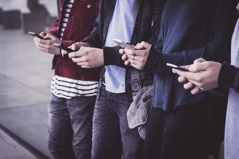 Group of young people watching smart mobile phones at the underground stop - Young people addiction to new technology trends - A royalty free stock image