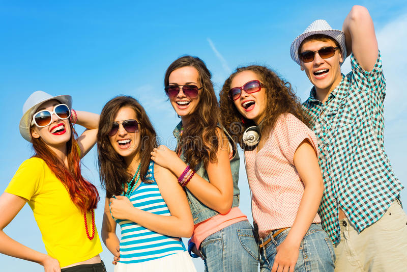 Group of young people wearing sunglasses and hat. S hugging and standing in a row, spending time with friends royalty free stock photography