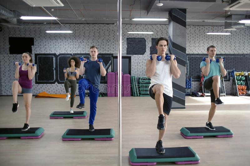 Group of young people working out with dumbbells and steppers in gym stock photos