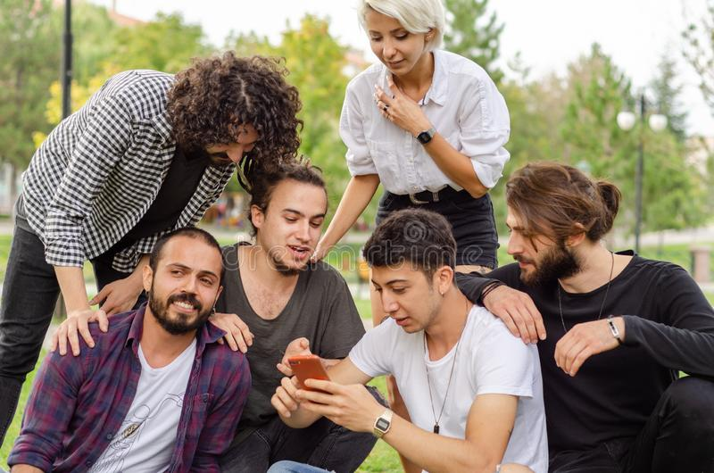 A group of young people are working in the park with mobile phones.They watch the phone carefully royalty free stock photo