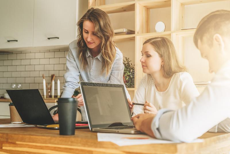 Group of young people working together. Man is using laptop, girls looking on screen of laptop, discussing business plan. Brainstorming, teamwork, startup royalty free stock photo