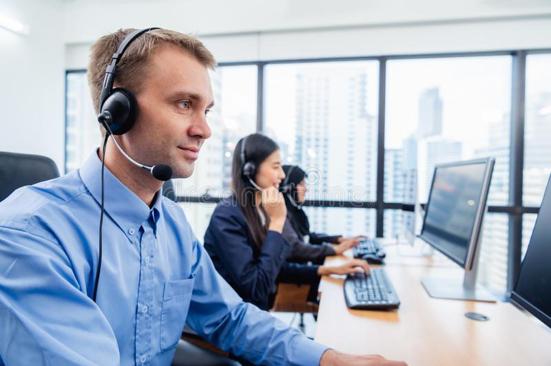 Group of young profession call center operator agent with headsets working in office. Business telemarketing service people royalty free stock photo