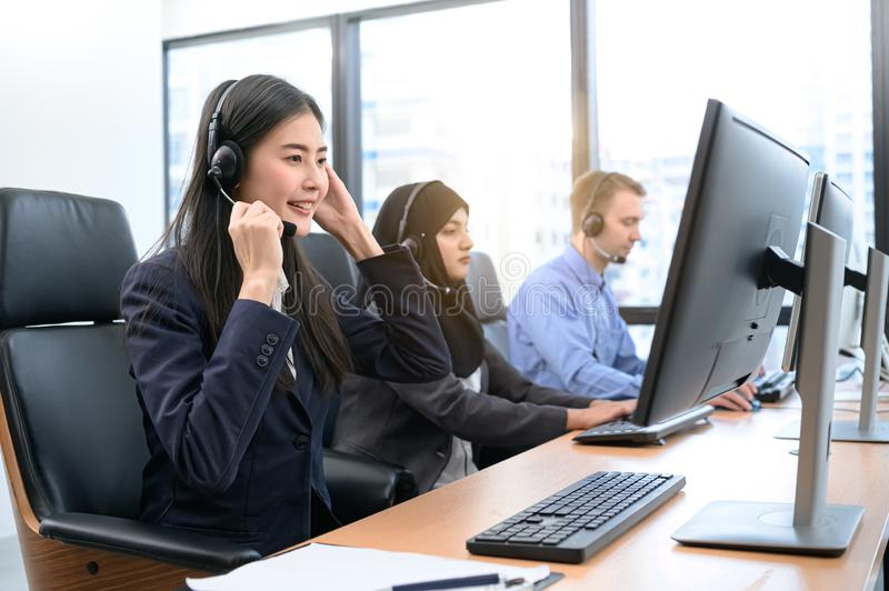 Group of young profession call center operator agent with headsets working in office. Business telemarketing service people royalty free stock images