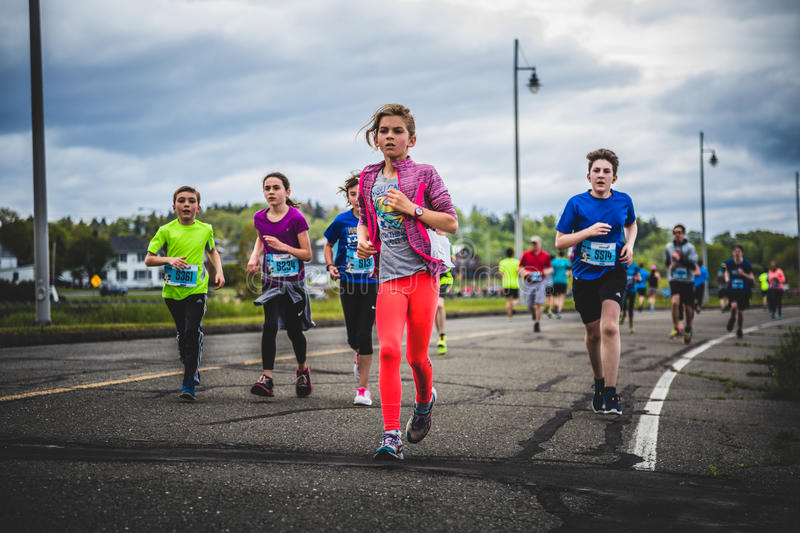 Group of Young Runners and Kids Racing Together. CARLETON, CANADA - June 4, 2017. During the 5th Marathon of Carleton in Quebec, Canada. Group of Young Runners royalty free stock image
