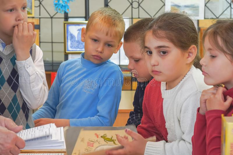 A group of young schoolchildren stand with books at the table stock photos