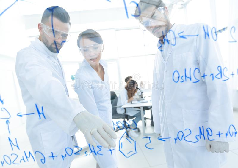 Group of young scientists talking in a lab stock image