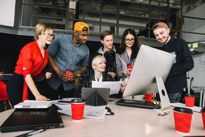 Group of young six business people and software developers in casual outfit working as a team in loft office stock photo
