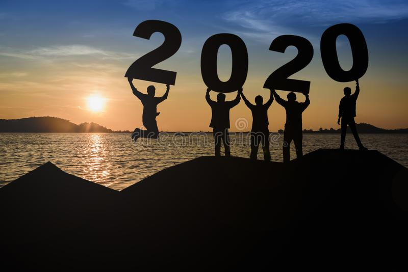 A group of young, sleek silhouettes of people who look happy and ready to hold the numbers 2020 and sunset as the background royalty free stock photography