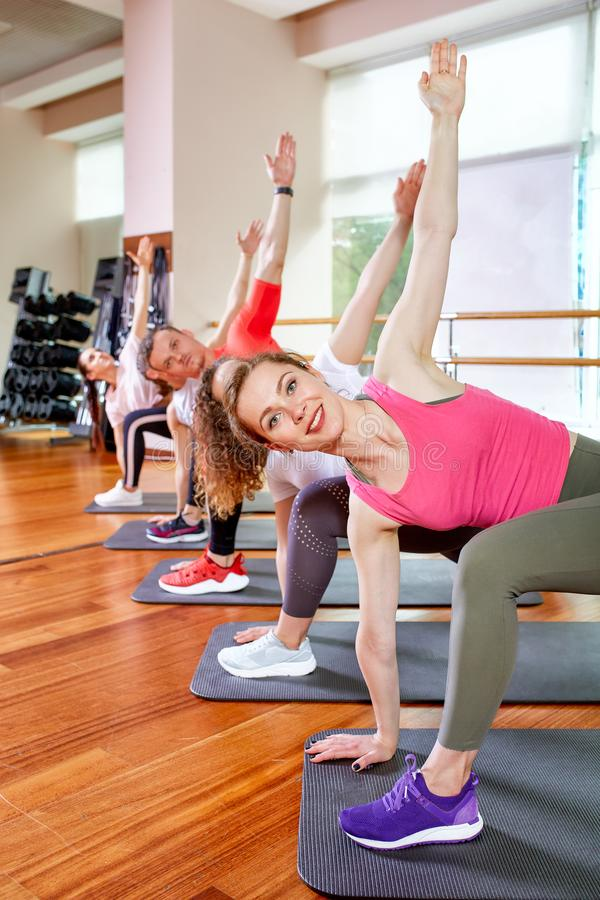 Group of young sporty attractive people practicing yoga lesson with instructor, standing together in exercise, working. Out, full length, studio background stock photo