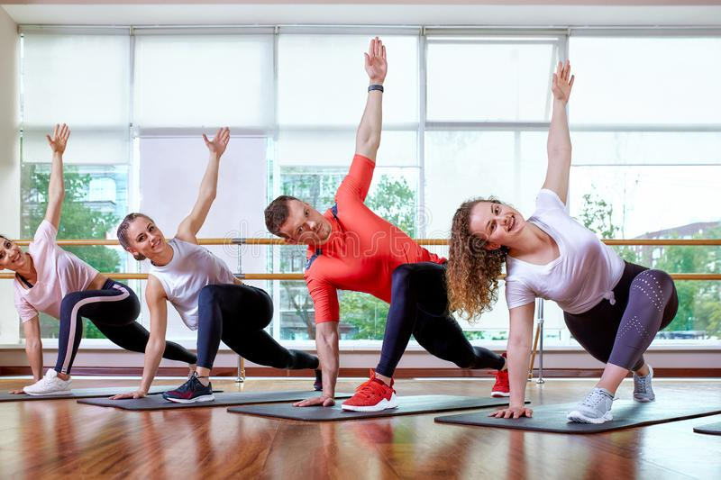 Group of young sporty attractive people practicing yoga lesson with instructor, standing together in exercise, working. Out, full length, studio background stock image